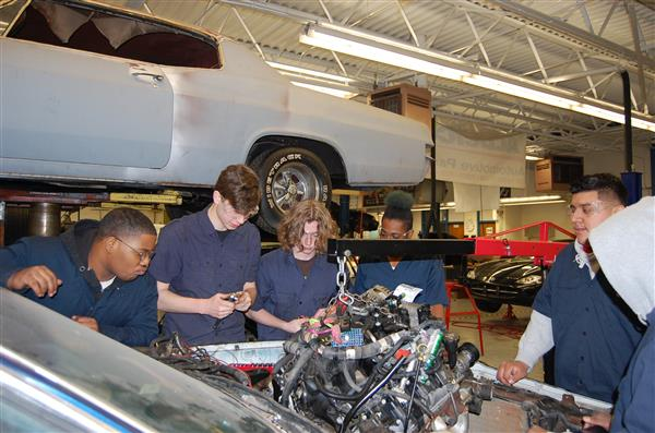 Students working under hood of car